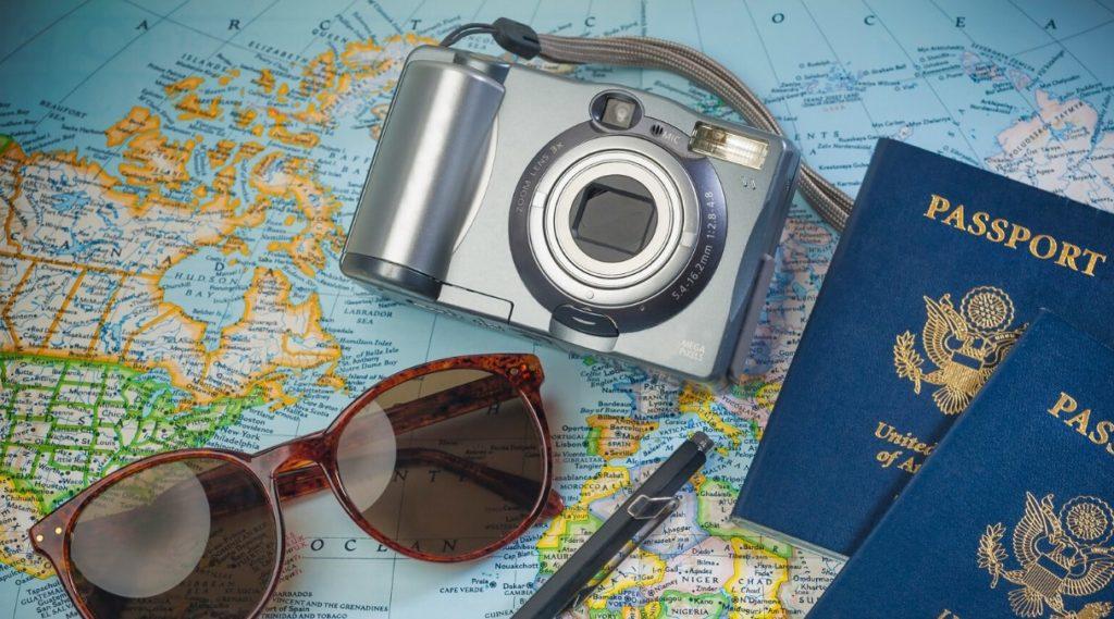 kamera, solbriller og pass over verdenskart