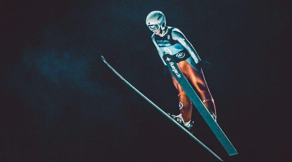 gutt som hopper på ski
